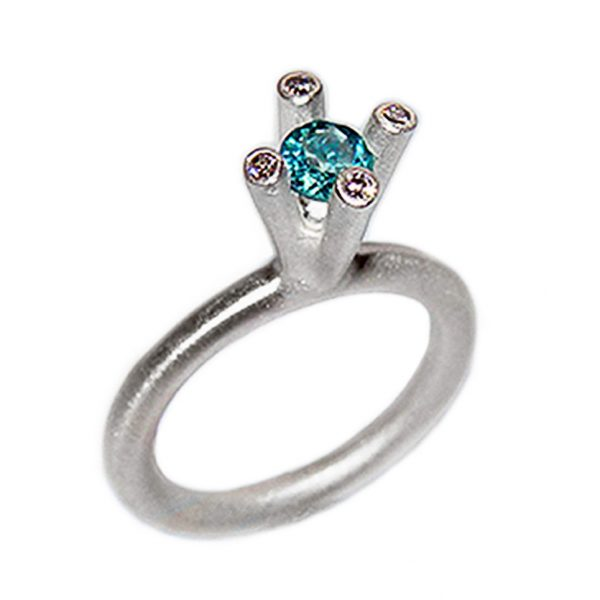 The 4 branch bough ring is bold and majestic in design and is inspired by nature. The silver ring has a comfortable rounded band of 3mm and the setting consists of a 5mm gemstone encircled by 4x 0.02ct diamonds (height of setting when worn is approx 8mm). The featured image shows a 5mm blue topaz. The ring comes with a variety of gemstones for example amethyst, iolite, citrine, peridot & garnet.