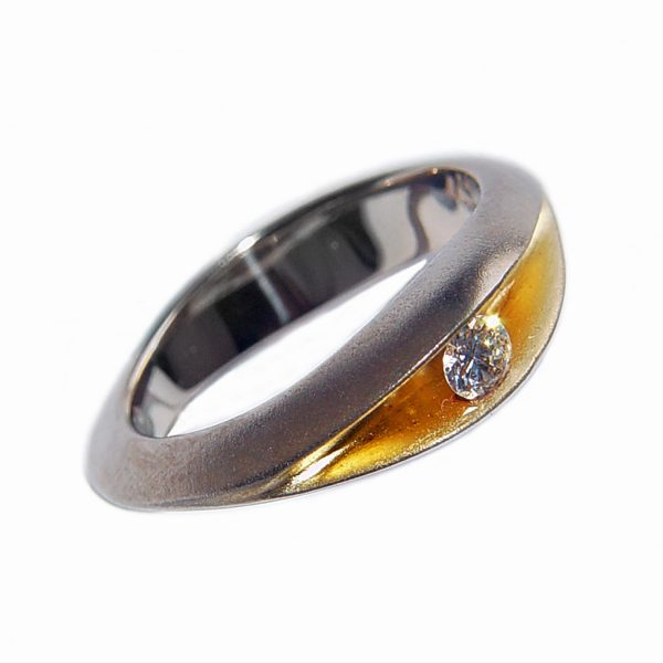 10pt 18ct gold diamond shell ring.The 18ct white gold ring is split across the top and has a solid band at the back. A sparkling diamond (0.1ct vsfg) glistens from within the rich 22ct gold plated interior. Approximate maximum dimensions are 5mm width & 5mm depth.The ring usually comes in a satin finish. There is also an 18ct gold diamond shell ring available in yellow gold version. Please contact for further details. The ring is elegant and unusual and therefore makes the perfect engagement or dress ring.