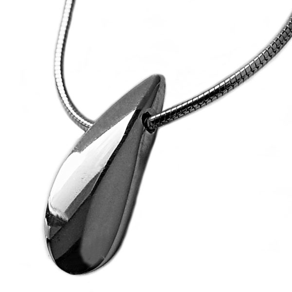 The plain side shell pendant has a smooth organic form. It is approx 22mm long with a width of 4mm and a depth of 8mm at the widest point. The pendant comes on a silver snake chain.
