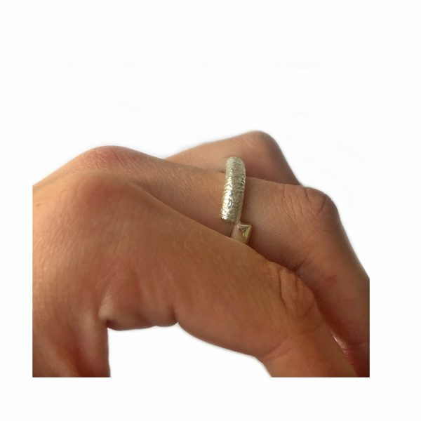 The off set band is a perfectly balanced silver ring of two halves, rough and smooth. The solid silver ring is one of Paul's original designs.The versatile band can be worn with the two halves top & bottom or twisted to create a completely different look. It is approximately 5mm wide and comes in a satin or polished finish.