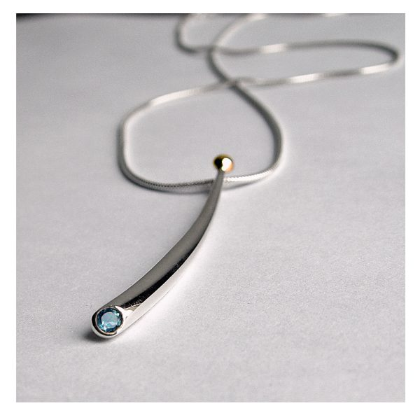 Long curved wiggly pendant with 3mm blue topaz & 18ct gold bead. The solid silver pendant tapers from 4mm and is approx 50mm long. It comes on a silver snake chain.