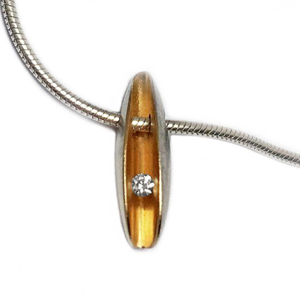 Small front diamond pendant. A lovely and unusual dainty diamond shell pendant in sterling silver. A brilliant 0.02ct diamond is captured within the two silver folds and contrasts perfectly with the rich 22k gold plated interior. The diamond is tension set to allow maximum light around the stone. This simple elegant pendant is perfect for all occasions and also makes a wonderful gift. Brilliant 0.02ct vsfg diamond tension set in satin finished sterling silver with contrasting 22k gold plated interior. Dimensons are 14mm in length, 4mm width and 6mm depth. The pendant has a Paul Finch hallmark and conforms to the British hallmarking standard & It is delivered in a Paul Finch Jewellery gift box. The pendant usually comes on a silver snake chain.Please let us know if you would like a 16'', 17', 18'', or 20'' chain when you place your order.