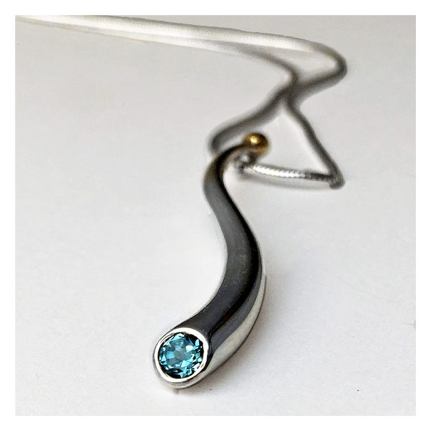 An elegant long curving wiggly pendant with 4mm faceted blue topaz and 18ct gold bead on a silver snake chain. The solid silver wiggly pendant tapers from 5mm and is approx 50mm long. The sweeping curves enhance the beautiful pure design.