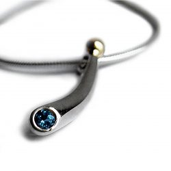 Small curved silver pendant with 3mm blue topaz & 18ct gold bead. The solid silver pendant tapers from 4mm and is approx 25mm long. It comes on a silver snake chain.