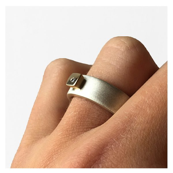 Silver 18ct ring HRW1AG. This solid silver ring has contrasting 18ct yellow gold detail and a sparkling 0.02ct vsfg diamond. The band is 7mm wide and has a depth of approx 2mm. The ring is practical and comfortable to wear(An all silver version is also available on request). Silver 18ct ring HRW1AG is individually handmade to order and comes in a wide range of sizes including 1/2 sizes. Please let us know your ring size when you place your order.We use the UK/AU sizing system, however. If you have a ring size based on EU, US/Canada or any other international sizing system we can convert it. The silver diamond ring has a Paul Finch hallmark and conforms to the British hallmarking standard. It comes in a Paul Finch jewellery gift box. Cleaning instructions For satin finish use silver dip, rinse in warm soapy water, dry thoroughly. For polished finish use silver polishing cloth/ and or silver dip. FREE Delivery The parcel will be sent out using secure Colissimo International tracked and signed for service and requires a signature on receipt. Dispatched within 2-5 working days