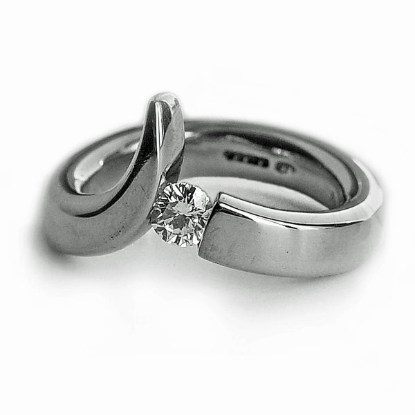 The 18ct diamond point ring is elegant yet simple in design. The solid 18ct white gold ring has been handforged from 4mm wire and features a tension set 25pt (0.25ct) VSFG Diamond. The solid gold ring is approx 4mm wide and has a depth of 3mm. It is unusual and stunning and makes the perfect engagement ring (in addition there is also a complimentary wedding ring Code C66). The ring is individually handmade to order. Please let us know your ring size when you place your order. Ring sizes H-P (including 1/2 sizes). We have used the UK/AU sizing system, however. If you have a ring size based on EU, US/Canada or any other international sizing system it can be converted. The ring is also available in 18ct yellow gold or platinum – prices on request. The 18ct gold point ring has a Paul Finch hallmark and conforms to the British hallmarking standard. It is delivered in a Paul Finch jewellery box