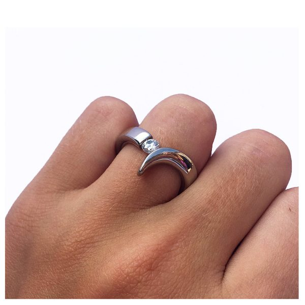 The 18ct diamond point ring is elegant yet simple in design. The solid 18ct white gold ring has been handforged from 4mm wire and features a tension set 25pt (0.25ct) VSFG Diamond. The solid gold ring is approx 4mm wide and has a depth of 3mm. It is unusual and stunning and makes the perfect engagement ring (in addition there is also a complimentary wedding ring Code C66). The ring is individually handmade to order. Please let us know your ring size when you place your order. Ring sizes H-P (including 1/2 sizes). We have used the UK/AU sizing system, however. If you have a ring size based on EU, US/Canada or any other international sizing system it can be converted. The ring is also available in 18ct yellow gold or platinum – prices on request. The 18ct gold point ring has a Paul Finch hallmark and conforms to the British hallmarking standard. It is delivered in a Paul Finch jewellery box.