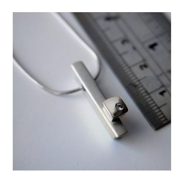 Solid silver ingot with silver detail set with solitary sparkling diamond (0.02ct vsfg). Approximate dimensions are length 24mm, width 4mm, depth 5mm. The pendant comes on a silver snake chain.