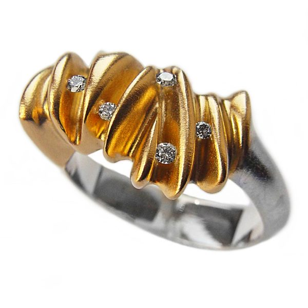 The 5 diamond sculptural shell ring is a stunning new addition to the collection. It is an unusual, elegant silver ring which has 5 brilliant vsfg diamonds (2x0.02ct, 3x0.03ct) set within golden waves. The solid silver undulating band has contrasting 22ct gold plating. Approximate maximum dimensions are 5mm at the back narrowing to 4mm and 12mm at the widest point of the top. The unusual sculptural ring is a perfect eternity ring or a statement ring suitable for every occasion.