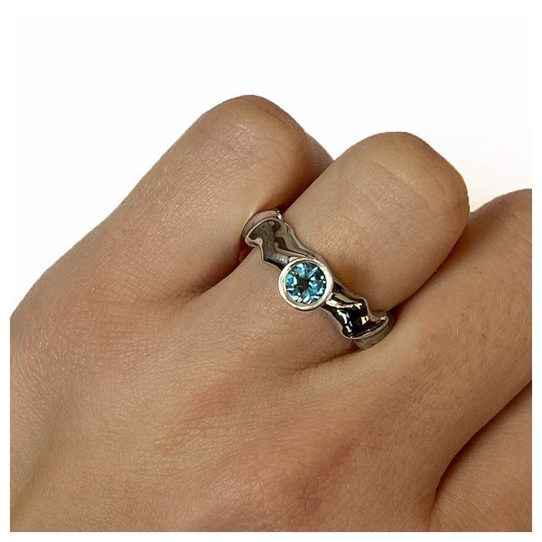 The silver gemset vine ring is striking and elegant. The centre piece of the ring is a sparkling 5mm blue topaz which compliments the delicate silver detailing of the band. The undulating band has a width of approximately 6mm at the widest point and a depth of approximately 2.5mm. The main picture shows the ring with blue topaz in a polished finish. If you would like an alternative gemstone our main choice includes blue topaz,amethyst, garnet, citrine, peridot, iolite. The ring is also available in a satin finish. The silver gemset vine ring is handmade to order to your specific finger size. Please let us know your ring size when you place your order. We have used the UK/AU sizing system, however. If you have a ring size based on EU, US/Canada or any other international sizing system we can convert it. The ring has a Paul Finch hallmark and conforms to the British hallmarking standard. It is delivered in a Paul Finch jewellery box. Cleaning instructions For satin finish use silver dip, rinse in warm soapy water, dry thoroughly. For polished finish use silver polishing cloth/ and or silver dip. FREE Delivery The parcel will be sent out using secure Colissimo International tracked and signed for service and will require a signature on receipt. Usually despatched within 2-5 working days